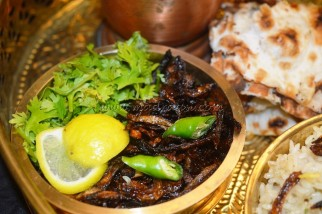 Fried onions with lemon slices, coriander leaves and green chillies