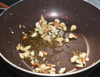 Thinly sliced nuts getting toasted in ghee/clarified butter